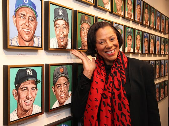 Cheryle Howard alongside the portrait of her father, famed Yankee Gold Glove-winner Elston Howard, displayed amid colleagues and competitors in the Yogi Berra Museum & Learning Center.