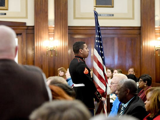 Jordan Woodard with the United States Marine Corps carries the American flag out of the courtroom after the presentation of the colors before the start of the Veterans Treatment Court graduation ceremony on Friday, Jan. 19, 2018.