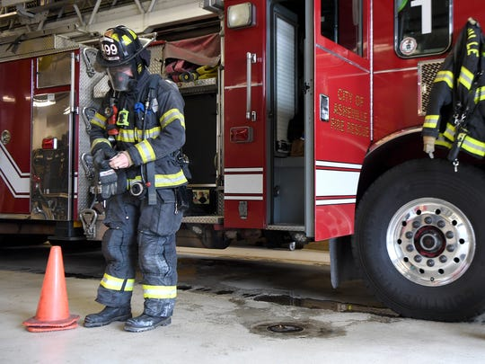 Matthew Kaylor demonstrates how much gear a firefighter wears when called out to a fire. Each firefighter is only issued one set of gear making it difficult to have the time to wash it between calls.