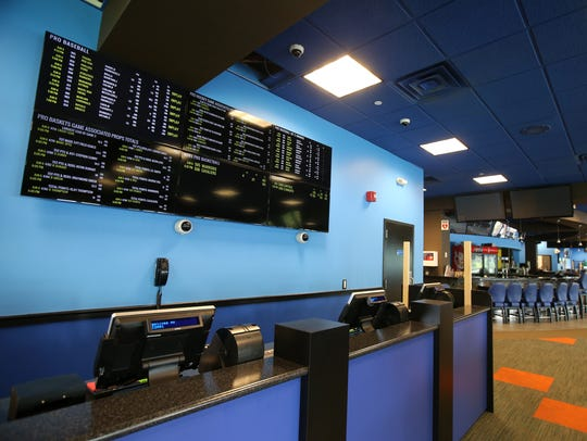 Sports betting odds are listed on the screens in preparation