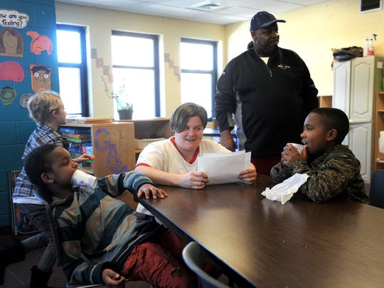 Kim Akbar, center, and Derrick Eddings work with a group of children during a spelling exercise at the YWCA off French Broad Avenue. The nonprofit's after school program relies on volunteers and paid staff for its success.