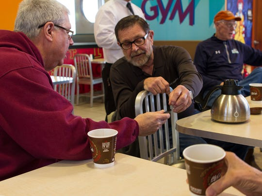 Jim Carlson and Del Johnson check out some photos on Johnson's smartphone at their morning coffee club.