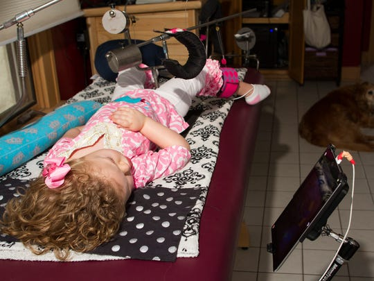 "Jacey Kloiber watches Disney's ""Lilo and Stitch"" on an iPad on Wednesday morning while exercising her legs in one of the many adaptive devices her parents Melissa and Allan Kloiber have engineered for her use."