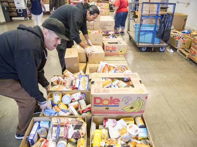 Ernesto Garcia, in front, packs food boxes at St. Mary's