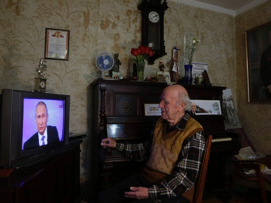A eldery man watches a TV broadcast of Russian President