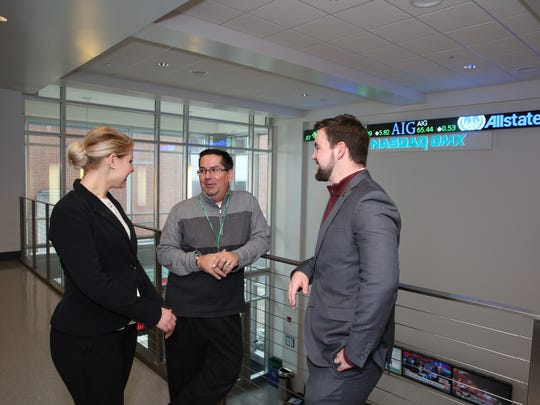 James Norrie, center, speaks with two students as the Dean of the Graham School of Business at York College.