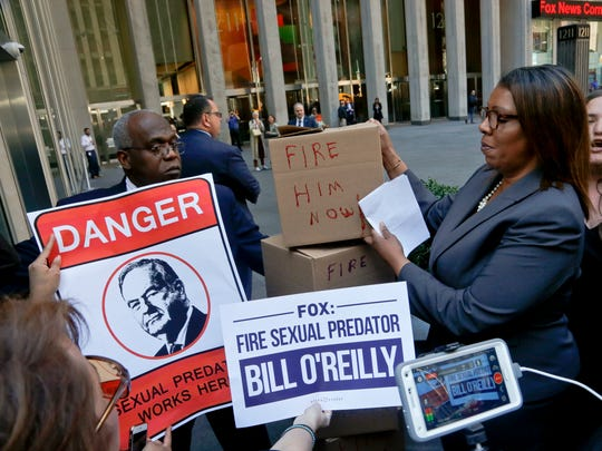 A security guard blocks an entry way as New York Public Advocate Letitia James, second from right, and protesters attempt to deliver boxes of petitions during a rally outside Fox News headquarters, calling for the network to fire Bill O'Reilly, on April 18, 2017, in New York.