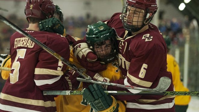 Eagles' defenseman Steve Santini (6) wraps up Catamount forward Jarrid Privitera (19) after the whistle during the men's hockey game between the Boston College Eagles and the Vermont Catamounts at Gutterson Fieldhouse in February.