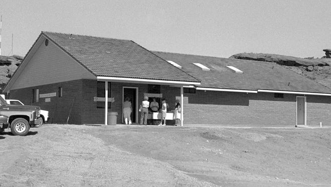 In June of 1989 the new St. George Animal Shelter was photographed for the Spectrum & Daily News as can be seen in the then image taken from the newspapers' archives. Controversy surrounded the shelter in the summer of 2013 when questions were raised by individuals and local animal welfare advocates regarding the treatment of animals within the facility and the condition of the building. By August of 2013, volunteers and city employees began making changes to the shelter. Outdoor kennels, non-existent in the then image and hidden by trees in the now image, were remodeled, an animal grooming station was added, raised beds for the animals were built, an outdoor cat enclosure was added and other structural improvements were made in order to bring the building into compliance with the American's With Disabilities Act. The landscaping was also improved around the building as can be seen in the now image taken by Spectrum & Daily News photographer Jud Burkett. Benches and plenty of shade now surround the building allowing volunteers to walk shelter dogs and play with them outside of the enclosed atmosphere of the shelter kennels. What is probably the most significant change in the animals shelter that can't be seen in the images is the fact that it is now a no-kill shelter.