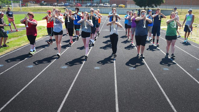 The Lincoln High School marching band trumpet section practices marching with their instruments during sectionals Monday, July 10, at the high school in Sioux Falls.