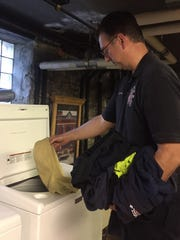 Mike Zyniecki does some of the station's laundry. All it takes to decontaminate clothing worn during fires and in the station is a regular washing machine.