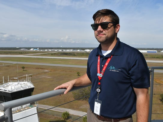 Rob Himler, airport communications manager, stands on the exterior catwalk of the new 115-foot air traffic control tower at Orlando Melbourne International Airport. In the background is the older, smaller tower.