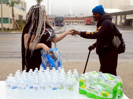 Akira Velalozano hands a free bottle of water to a man Friday, Dec. 16, 2016, at City Hall in Corpus Christi. City officials confirmed Thursday morning that one chemical contaminated the city's water supply.