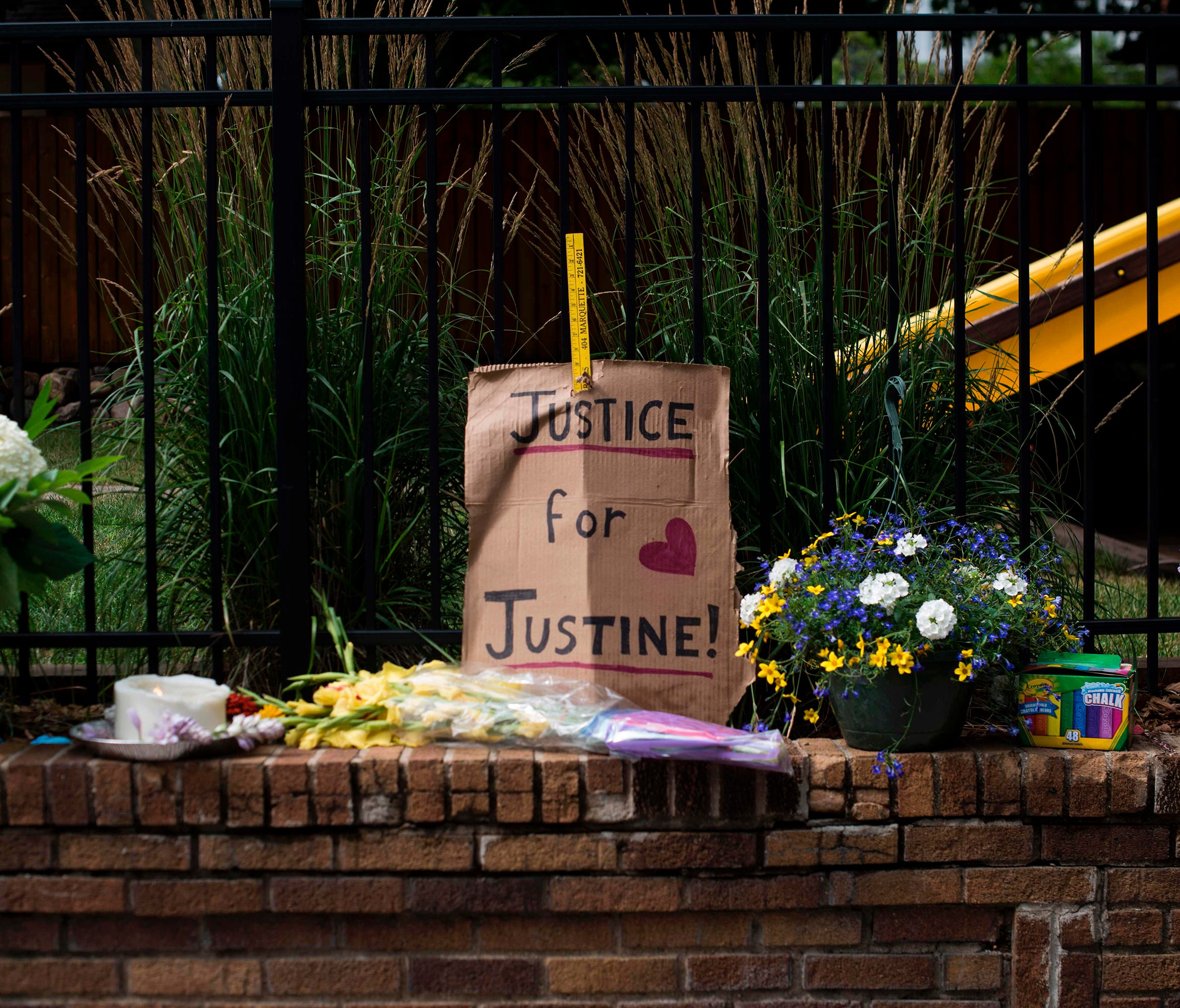 A sign and flowers are left at a makeshift memorial for Justine Damond on July 18, 2017, in Minneapolis.