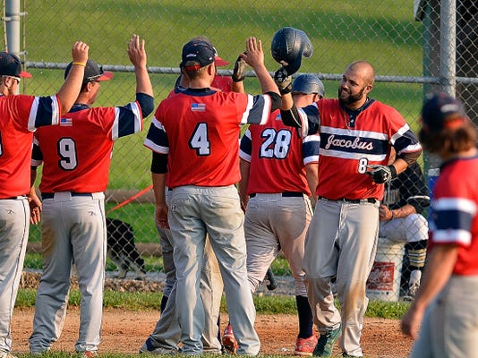 Jacobus players come onto the field to congratulate teammate Austin Calaman after he hit a solo homer against Red Lion during Susquehanna League baseball action on Monday. Jacobus won the game, 2-0.