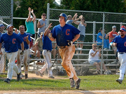 Conrads fans cheer and the team celebrates as  Joe Yourgal runs home to score the game-winning run on a hit by Josh Knaub, not pictured, against East Prospect during game four of the Susquehanna League playoff championship series Sunday in New Bridgeville. Conrads won, 7-6, in 11 innings to take the best-of-five series, 3-1. It was the 18th overall league playoff title for Conrads.