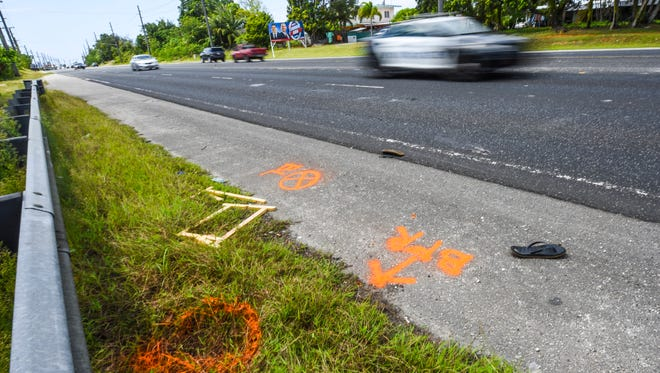 A Guam Police Department vehicle passes by paint markings and a pair of zories along Marine Corps Drive in Dededo on Wednesday, Mar. 7, 2018.