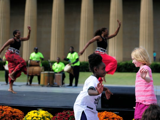 Zoe McCord 7, dances with Lucy Tizer 8, as African dancers perform during the Celebrate Nashville event at Centennial Park Saturday Oct. 4, 2014, in Nashville, Tenn.
