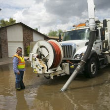 Michael Baldoneger, a City of Mesa equipment operator, operates a truck to remove standing water on a flooded street.