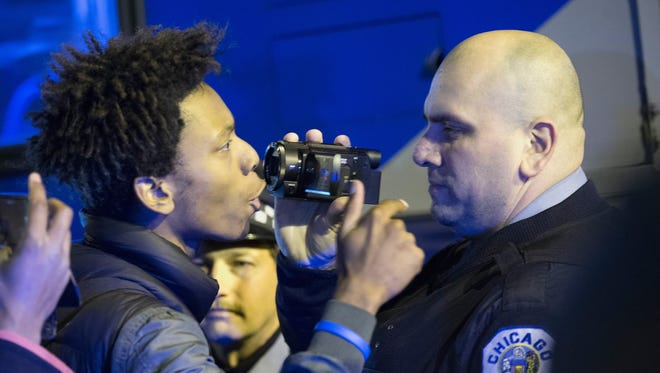 Demonstrators confront police during a protest Nov. 24, 2015, following the release of a video showing Chicago Police officer Jason Van Dyke shooting and killing Laquan McDonald in Chicago.
