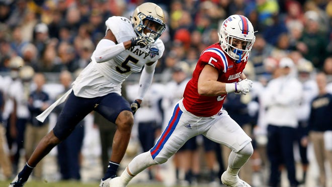 Louisiana Tech Bulldogs wide receiver Trent Taylor (5) runs with the ball while chased by Navy Midshipmen linebacker Justin Norton (5) in the first quarter at Amon G. Carter Stadium.