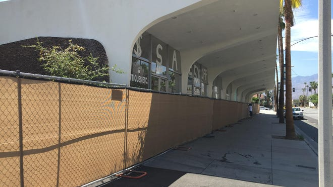 The modernist commercial and retail building near the corner of South Indian Canyon Drive and Ramon Road in Palm Springs is now surrounded in construction fencing to prevent trespassers.