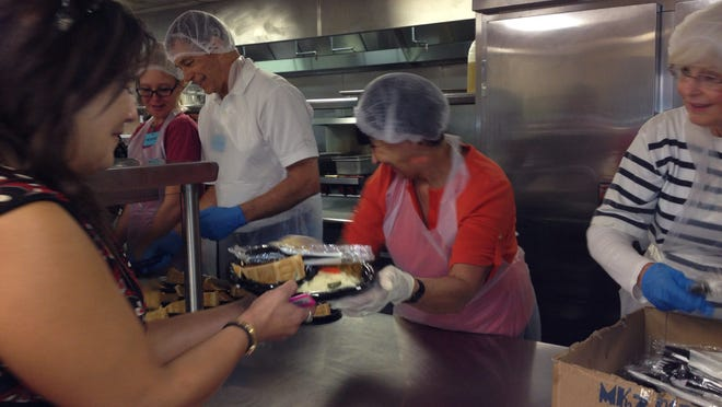 Lou Salute, center, and Terri Kirshner, both of La Quinta, were among the volunteers serving Thanksgiving meals to those in need Thursday morning at Martha's Village and Kitchen in Indio.