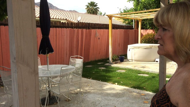 Diane Scurlock of La Quinta looks at her backyard fence, which was warped in parts during the Sept. 8 storm that flooded her cove neighborhood off of Eisenhower Drive.