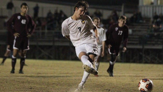 Above: Lincoln senior Jamison Ingram strikes a penalty kick for a goal, his third of Thursday's night game against Chiles. The Trojans won 4-2, rallying from a one-goal halftime deficit.