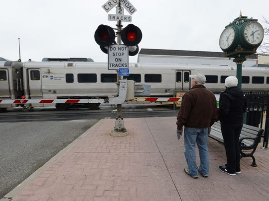 Ramsey's Main Street train station crossing and its dangers. Car traffic often backs up across the tracks, creating frequent near-accidents. A man and woman waiting for a commuter train to pass so they can cross heading east in Ramsey, NJ. December 06, 2016.