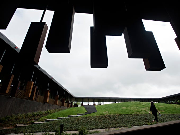 A pedestrian walks through the National Memorial for