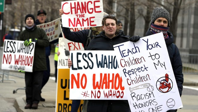 Protesters hold signs urging the Cleveland Indians to change drop use of the team's mascot, Chief Wahoo, before a recent home opener in Cleveland.