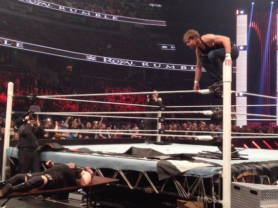 Deam Ambrose prepares to go airborne while Kevin Ownes lays helpless on a folding table below.