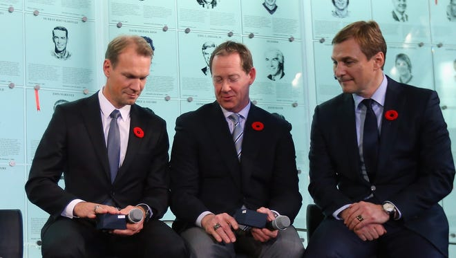 (Left to right) Nicklas Lidstrom, Phil Housley and Sergei Fedorov look at their Hockey Hall of Fame rings at a press conference November 6, 2015 in Toronto.