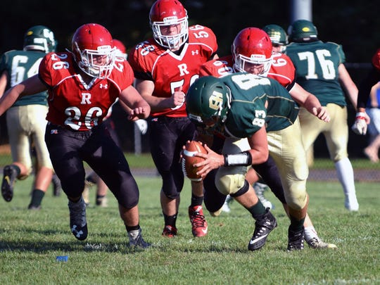 From left, Riverheads defenders Dalton Jordan, Alex Diehl and Bryan Hostetler bring down East Hardy, W.Va., quarterback Clay Skovron during their scrimmage at the Riverheads Jamboree on Saturday, Aug. 19, 2017, at Riverheads High School in Greenville, Va.