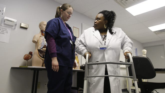 Instructor Tiffany Hicks-Sims, right, demonstrates how to use a walker for student Heather Tompkins during a class at Everest Institute in Irondequoit in this 2010 photo.