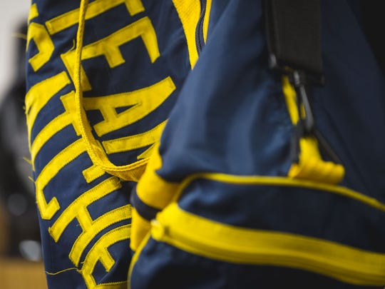 A Team Foxcatcher bag hangs loosely on a shelf inside