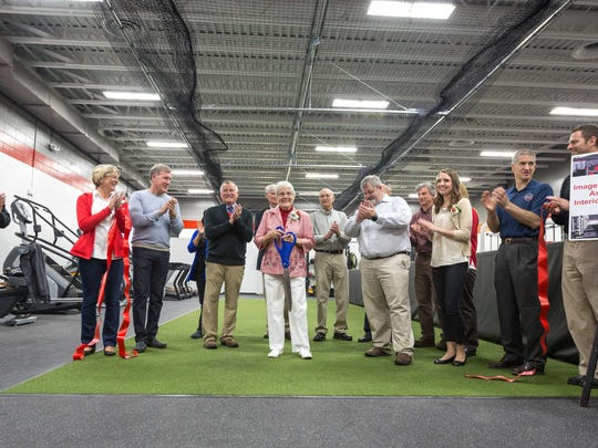 Pat Raczek, wife of coach Bob Raczek and long-time Pacelli supporter, cuts the ribbon as the Pacelli High School unveils a new fitness center on May 10, 2017.