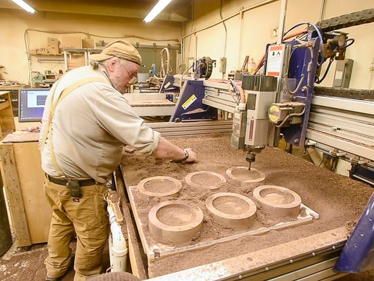 Randy Ouellette clears sawdust away as an automated