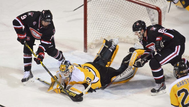 Colorado College goalie Tyler Marble covers the puck as St. Cloud State's Joey Benik (9) and Patrick Russell (63) try to get to it last season in an NCHC game at World Arena in Colorado Springs, Colorado.
