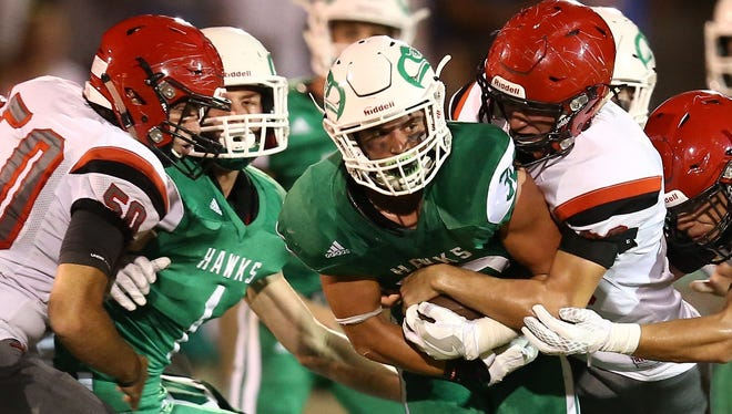 Wall fullback Tymber Carr, center,  battles and grinds out first down yardage against a swarm of Eastland Mavericks defenders Friday in Wall.