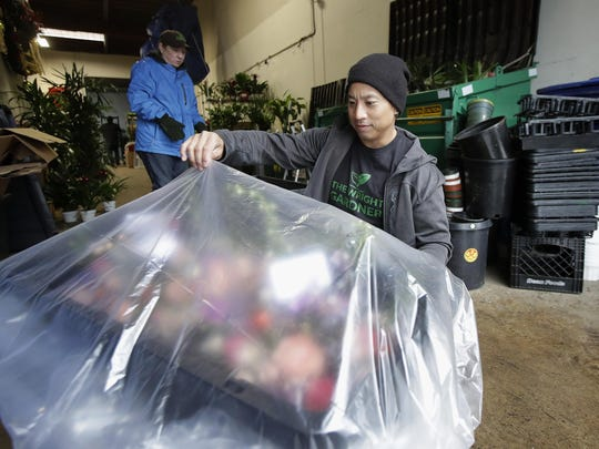 In this Wednesday, Feb. 13, 2019, photo The Wright Gardner operations associate Jason Biting, right, and operations supervisor Maureen Grady prepare plants for delivery in South San Francisco, Calif.
