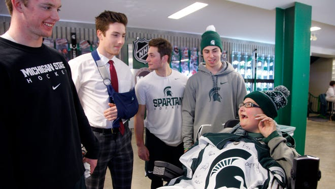 Michigan State hockey players from left, Tommy Apap, Brennan Sanford, Damian Chrcek and Anthony Scarsella present Brittany Van Hoogen with a jersey signed by the team, Saturday, Jan. 6, 2018, at Munn Arena for MSU's hockey game against Ohio State.