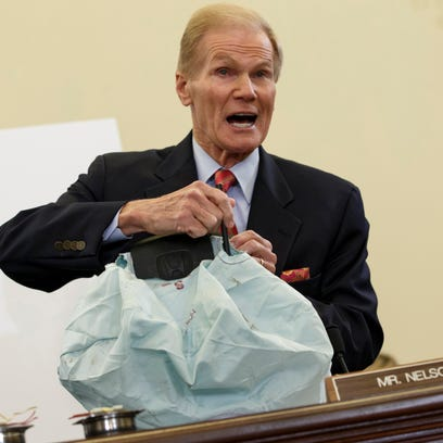 Senate Commerce Committee member Sen. Bill Nelson, D-Fla. displays the parts and function of a defective airbag made by Takata of Japan that has been linked to multiple deaths and injuries in cars driven in the U.S., during the committee's hearing on Capitol Hill in Washington on Nov. 20, 2014.