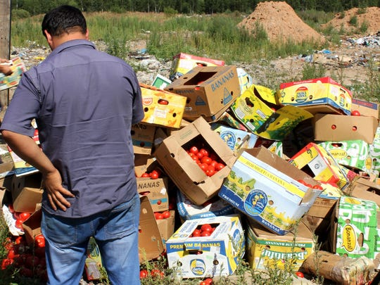 A man stands near packages of banned tomatoes near