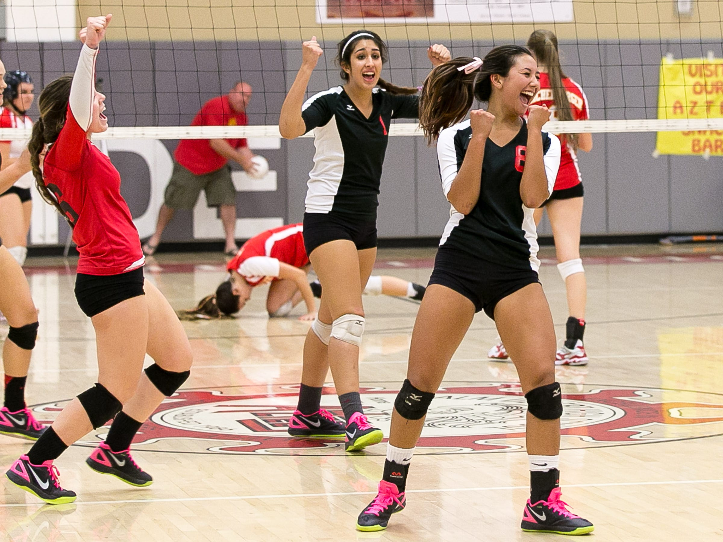 Palm Springs Asia O'Neil (right) reacts as she scores a point to force the match to a tiebreaker against Palm Desert on Thursday. Palm Springs won 3-2.