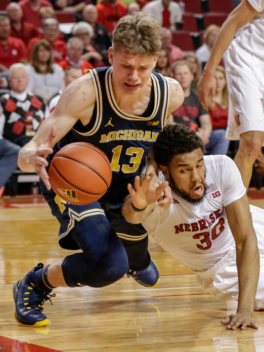 Michigan's Moritz Wagner (13) and Nebraska's Ed Morrow (30) scramble for a loose ball during the second half of an NCAA college basketball game in Lincoln, Neb., Sunday, March 5, 2017. Michigan won 93-57. (AP Photo/Nati Harnik)
