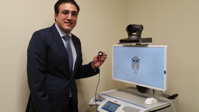 """Dr. Bobby Malik, M.D., Chief Medical Officer, Athene Telehealth based in Raritan, holds an e-stethoscope that is connected to a laptop on the company's 'telemedicine cart.'  The digital diagnostic tools make it possible for a patient suffering from shortness of breath, pain, or a worsening wound, to be examined and diagnosed from a distance by a physician who is able to hear the patient's heartbeat and lungs, and review all vital signs from anywhere in the world. Malik said, """"The high-resolution camera makes it possible for the doctor to zoom in to see, for instance, a wound or a rash, close up with great clarity."""""""