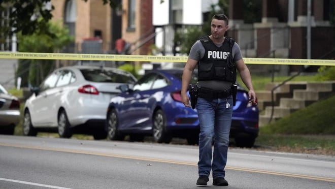 Police work near the scene of a shooting Saturday in St. Louis that left one officer dead and another wounded. The suspect, Timothy Kinsworthy Jr., was taken into custody after a lengthy standoff.