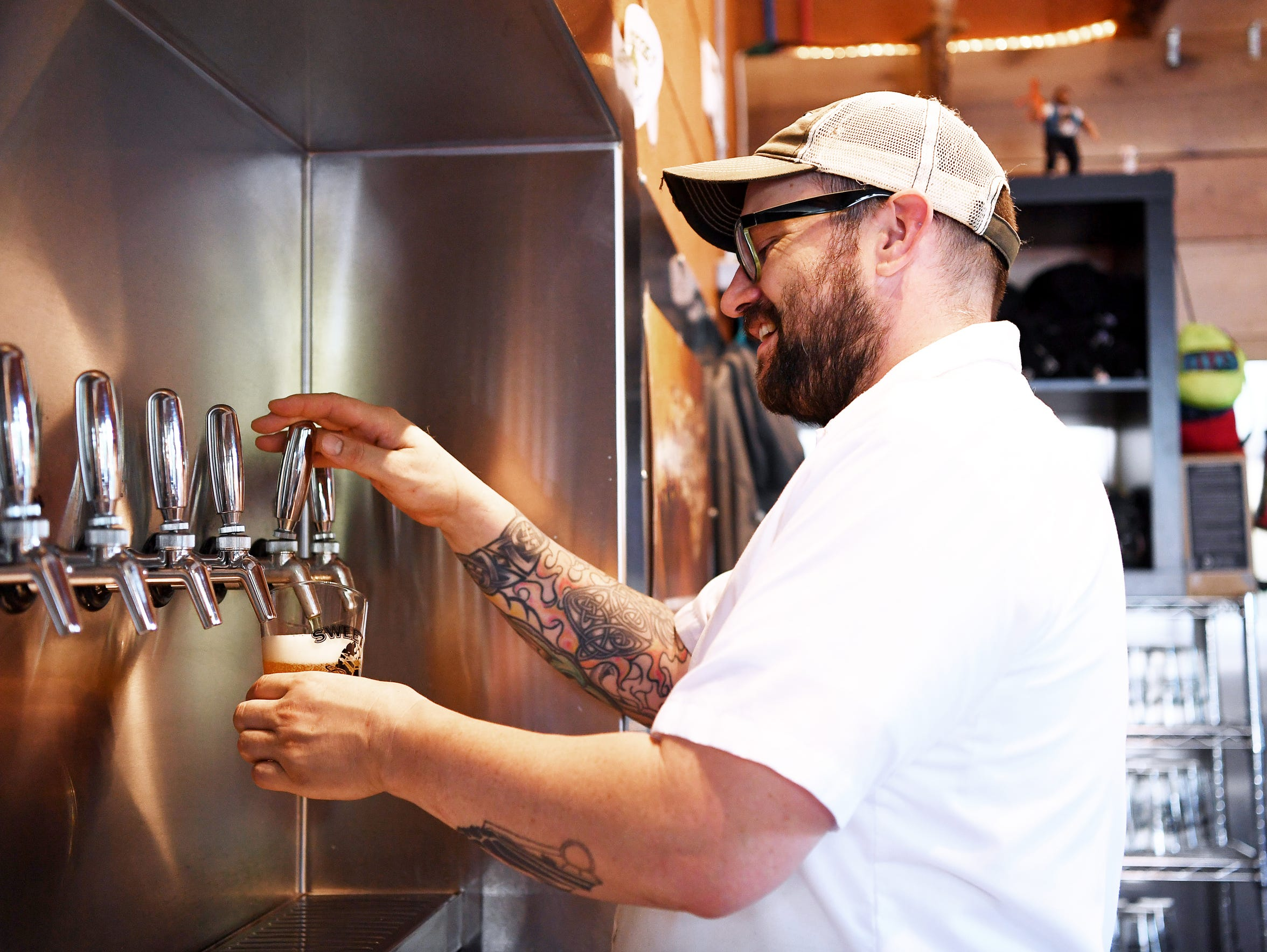 Chad Gibson pours a beer at Sweeten Creek Brewing July